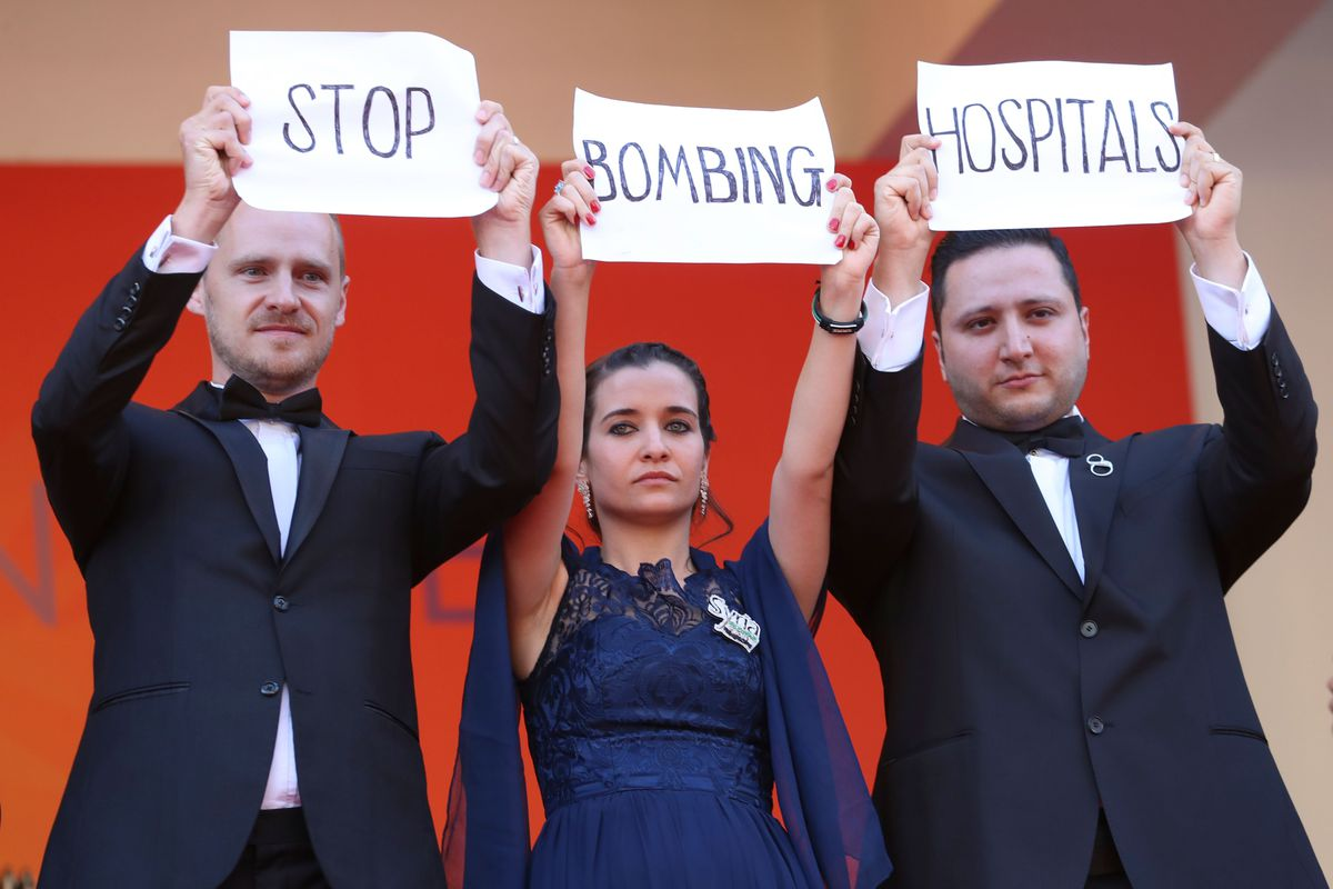 "Documentary filmmakers Edward Watts and Waad and Hamza Al-Kateab hold up signs that read ""Stop bombing hospitals."""