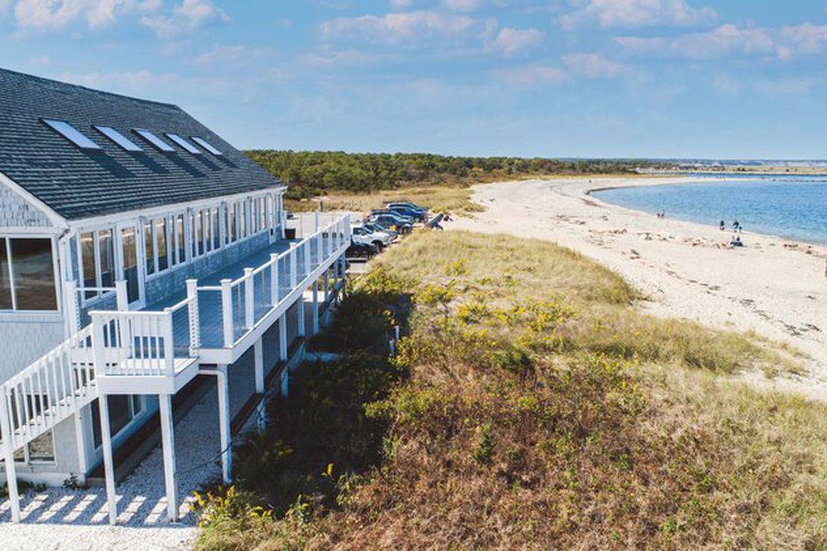 A two-story light blue building with a deck sits on a grassy beachfront area