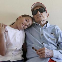 Cuban former pitcher Conrado Marrero, right, who once played with the Washington Senators, embraces his great-granddaughter Sandra Marrero as they pose for pictures during an interview in Havana, Cuba, Wednesday, April 25, 2012. Marrero, who last year became the oldest living former big leaguer, turned 101 on Wednesday.
