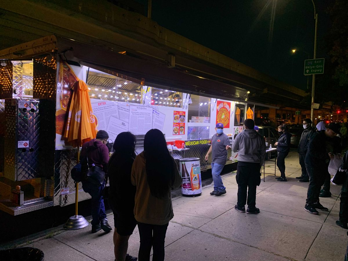 A line of people stands in front of a wide taco truck