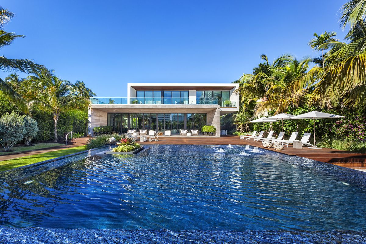 A gorgeous contemporary estate with a large infinity pool in the back and tropical modern design