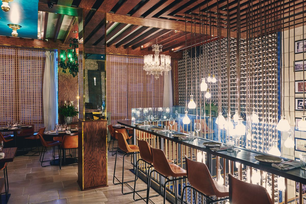 The interior of a restaurant with hanging lights, bar seats in wood, and a tiled wall