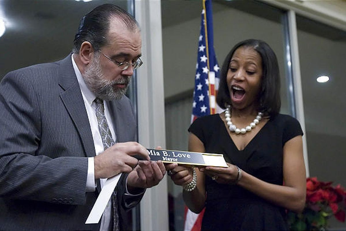 Outgoing Mayor Timothy Parker replaces his desk name plate with Mayor Mia Love's on Friday.