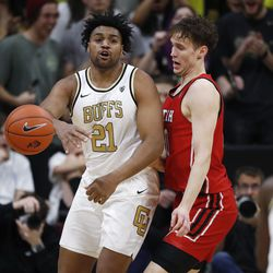 Colorado forward Evan Battey, left, passes the ball as Utah forward Mikael Jantunen defends in the first half of an NCAA college basketball game Sunday, Jan. 12, 2020, in Boulder, Colo.