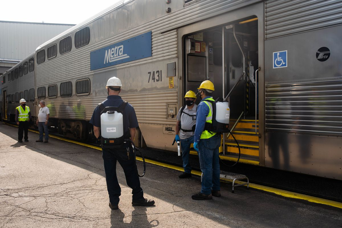 Cleaning crews stand near a Metra train at Metra's Western Avenue Coach Yard at 2801 W. Grand Ave. Tuesday morning, Sept. 15, 2020. Metra launched a campaign Tuesday that informs riders about the steps they are taking to keep their trains clean and their passengers safe amid the COVID-19 pandemic.