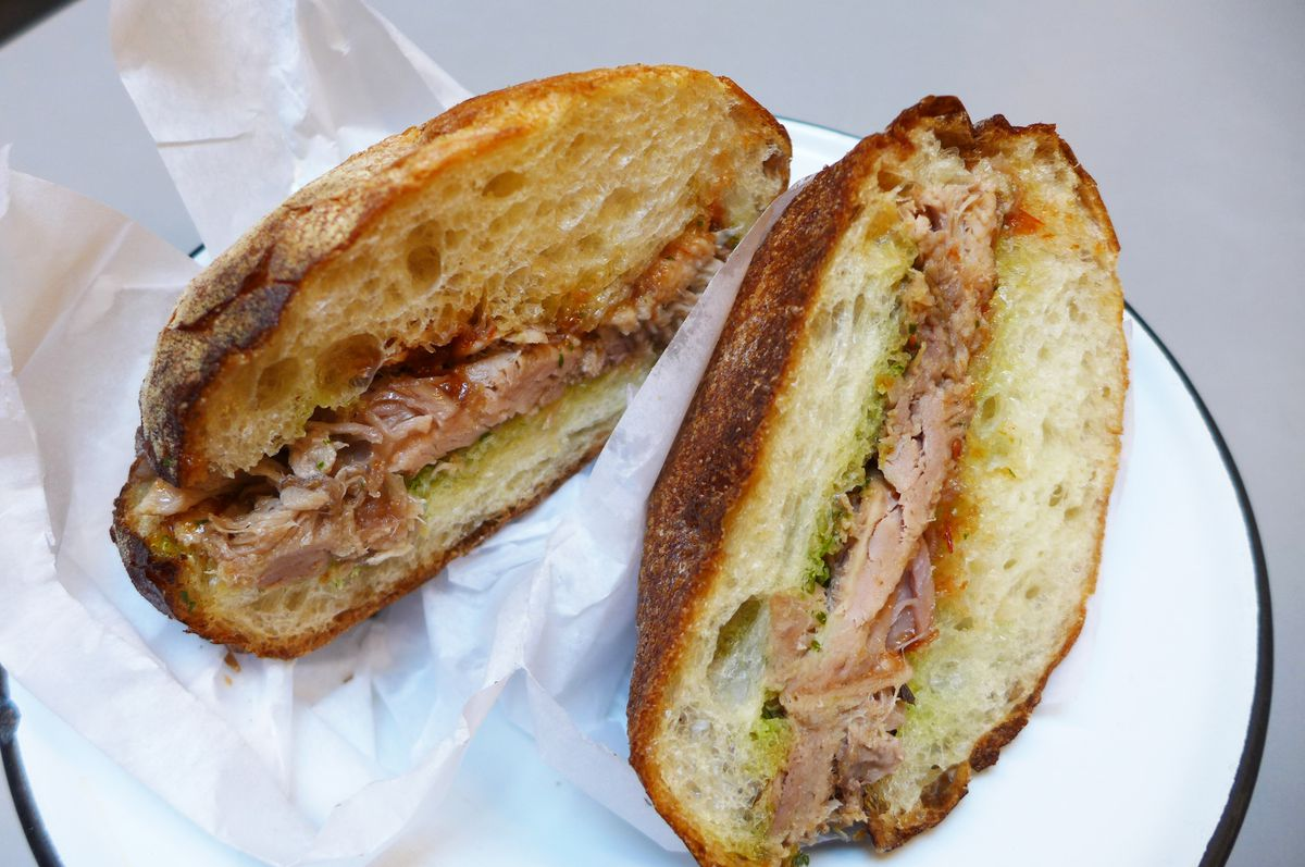 A cut sandwich on a roll showing the filling of pulled pork and sticky pink condiments...