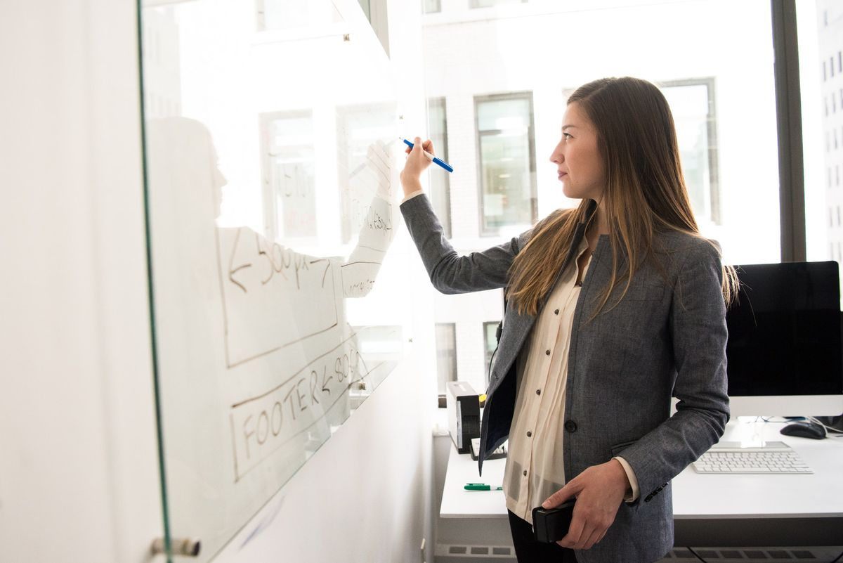 A teacher in a design class sketches out ideas on a whiteboard.