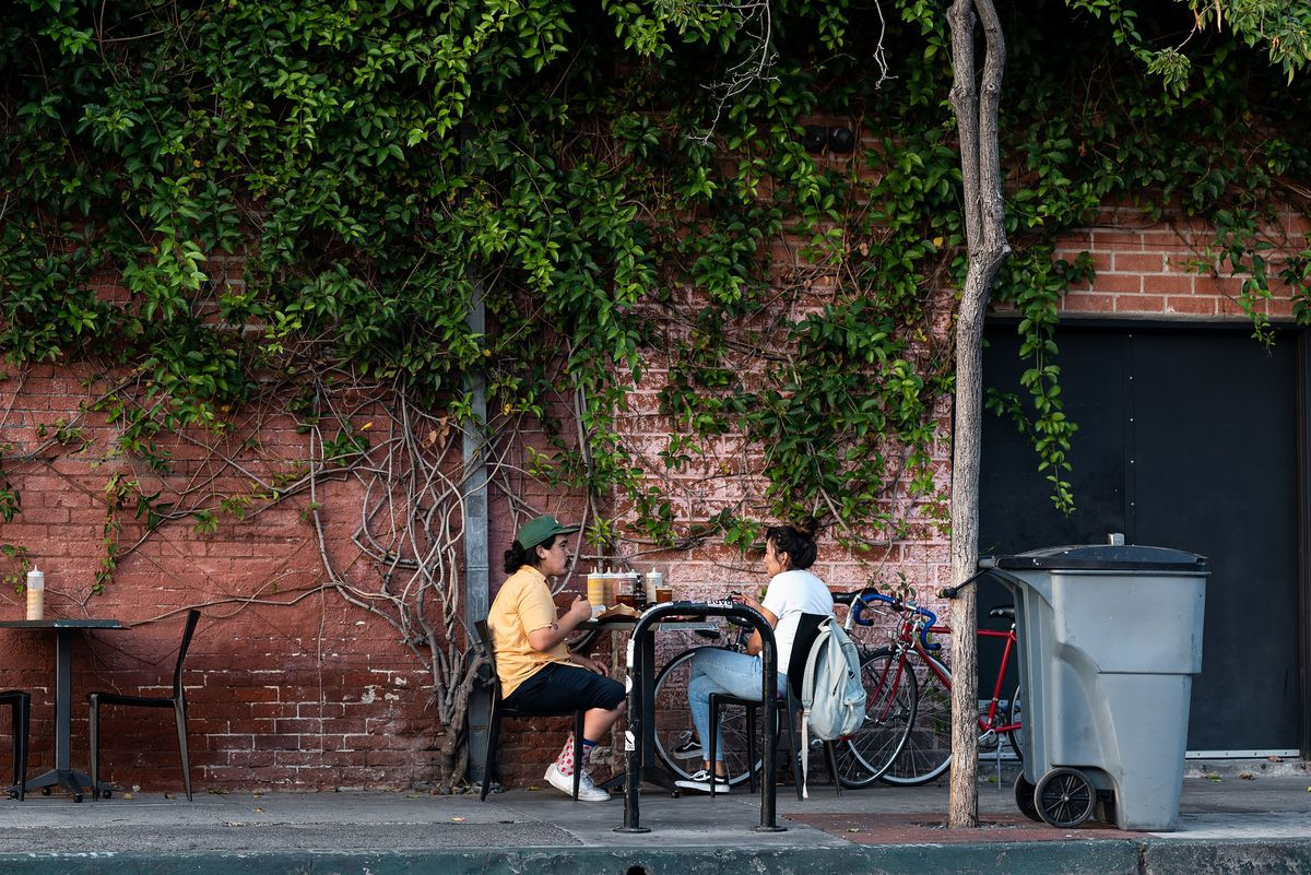 Couple sits outside at a table in LA's Arts District with greenery covering brick walls.
