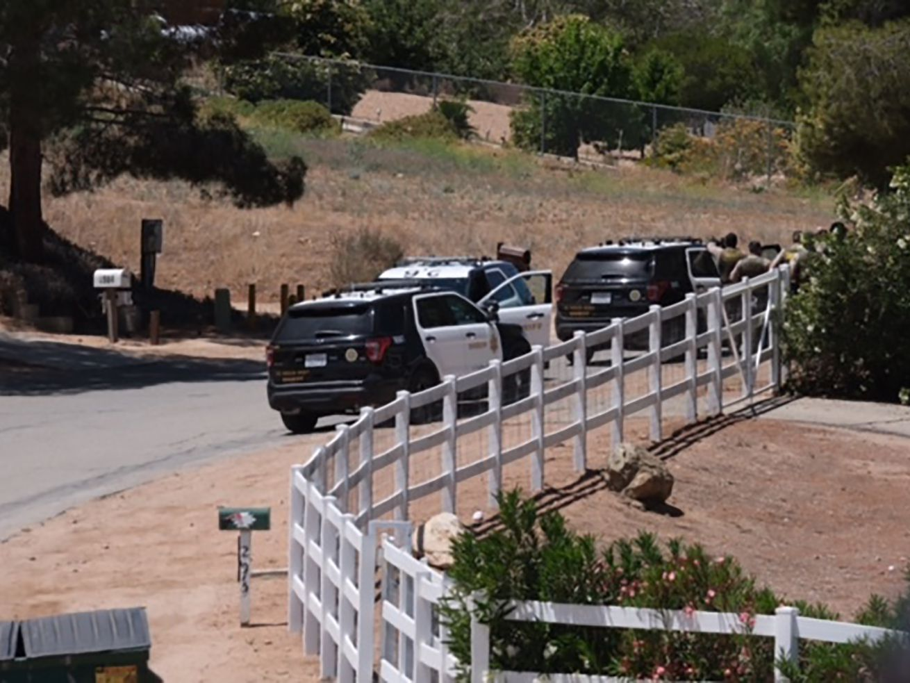 Police vehicles appear on the scene of a fire near a home in Acton, Calif. on Tuesday, June 1, 2021. Authorities say there's been a shooting at a Los Angeles County Fire Department station.
