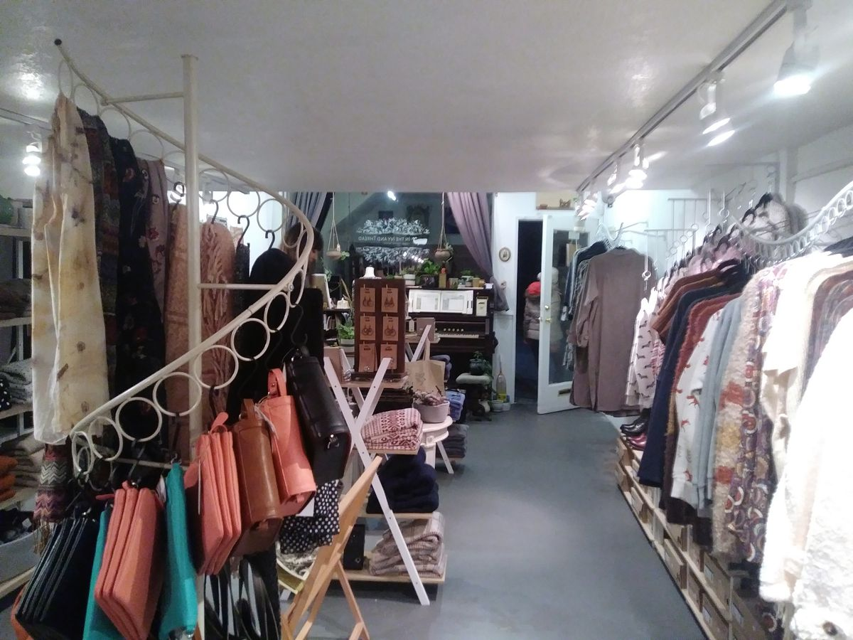 The interior of a shop. Clothing racks line the right wall, and to the left, a spiral-shaped rack has scarves and purses. Various other items are displayed around the store, including furniture and home textiles.