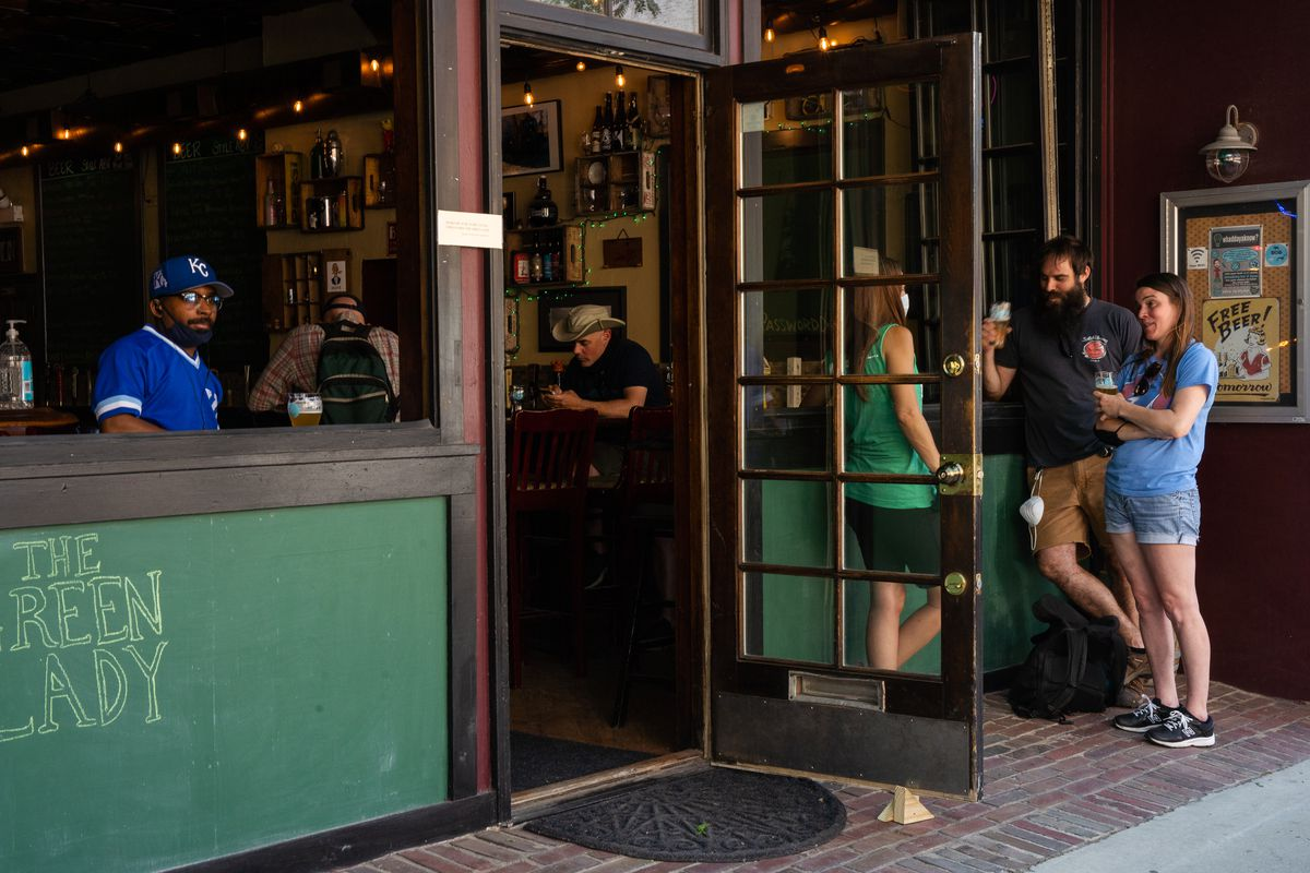 Christian Trezvant (left) and other customers chat and drink at The Green Lady tavern in Lake View on Wednesday, June 17, 2020.