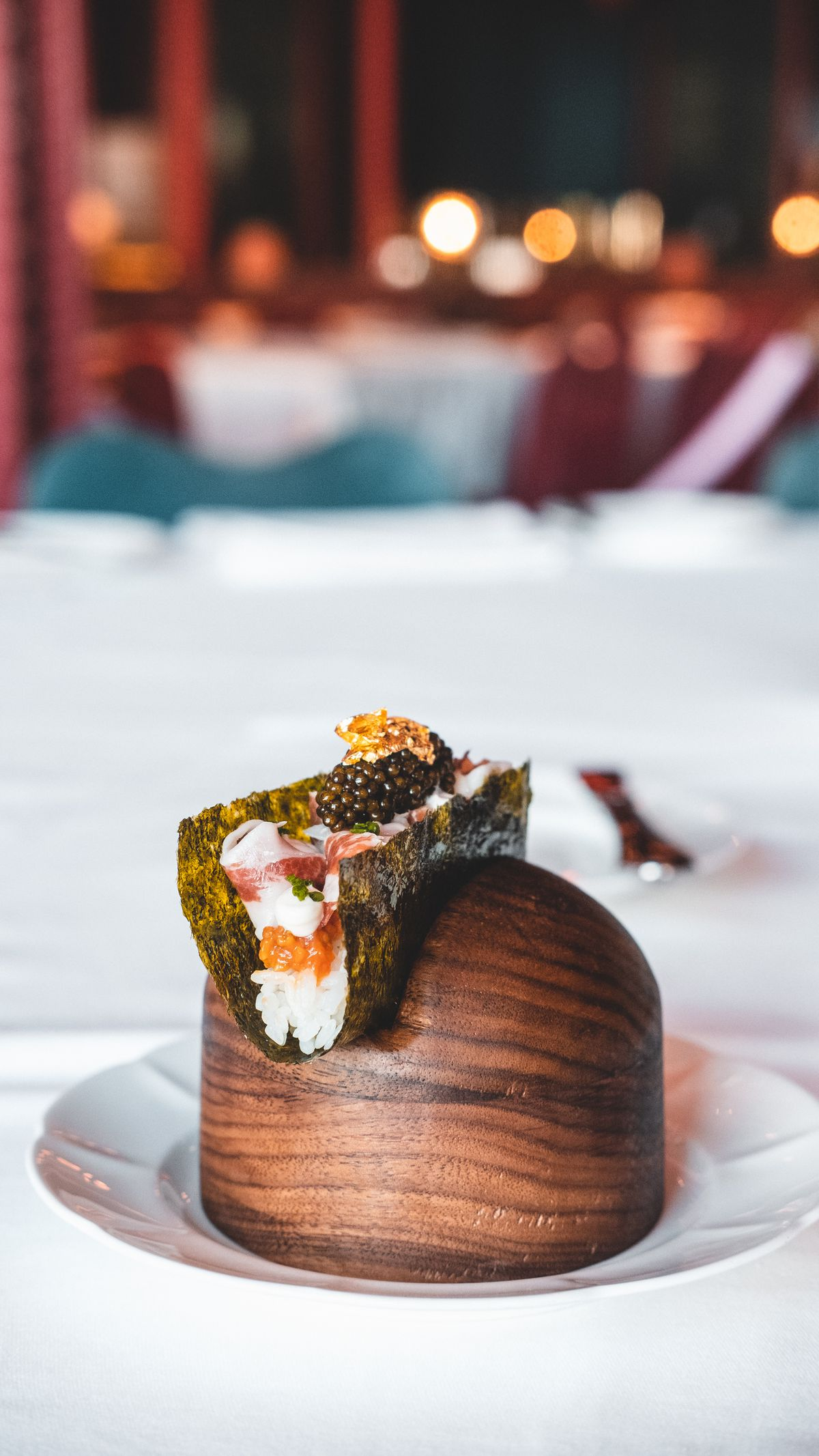 A hand roll with tomatoes and caviar.