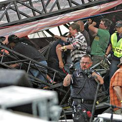 Police officers and others work to free people from the wreckage of the  main stage after it flipped in a storm during the Big Valley Jamboree in Canrose, Alberta Canada on Saturday.