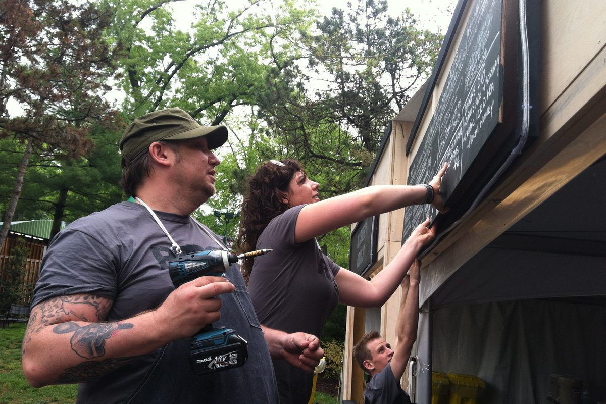 Chef RJ Cooper hangs the restaurant's menu board for the day, which featured festival fare, including corn on the cob, cheese steaks and arancini balls.