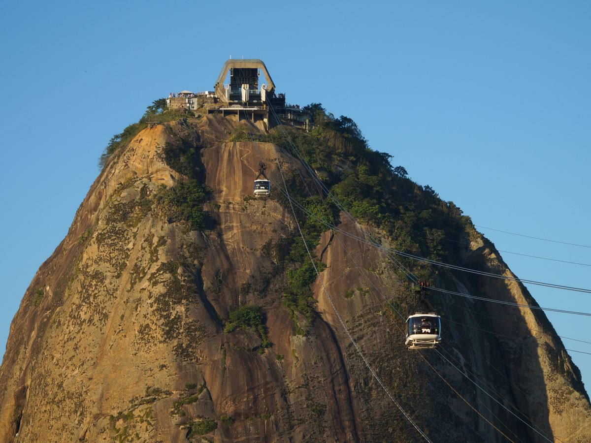 A view of Sugarloaf Mountain in Rio de Janeiro. There is a tram making its way up to the top of the mountain.