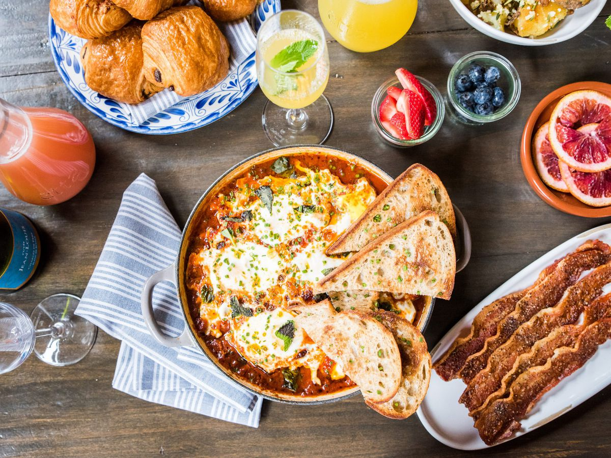 A variety of brunch dishes and drinks spread out on a table.