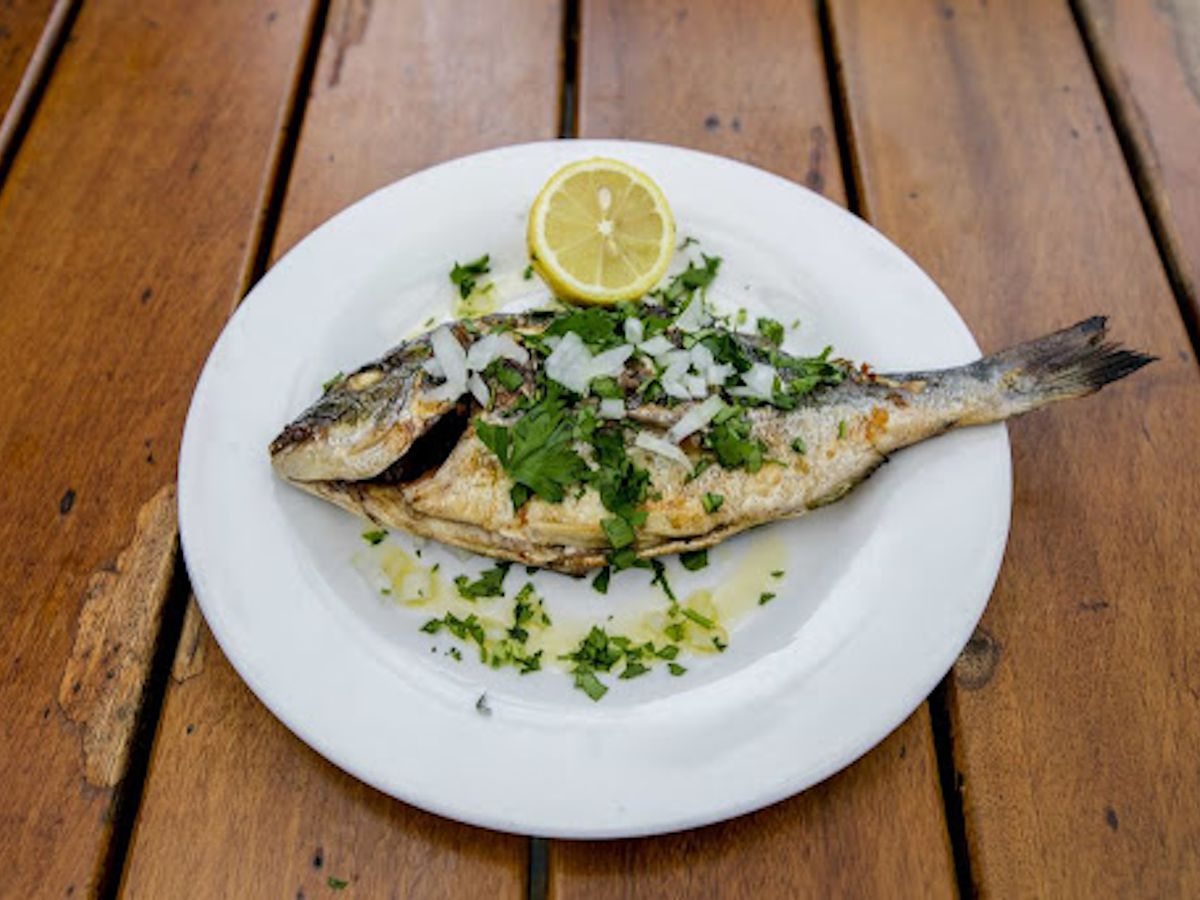 Grilled sea bream on a white plate, served with a scattering of parsley and a lemon at one of London's best Greek restaurants, Tsiakkos and Charcoal
