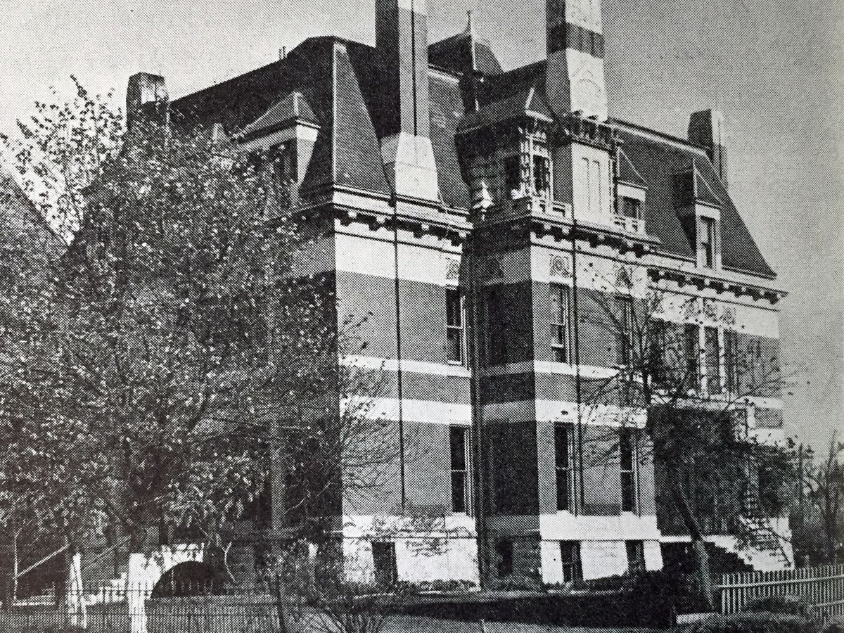 A large building with a red brick facade, multiple floors and windows, and chimneys.