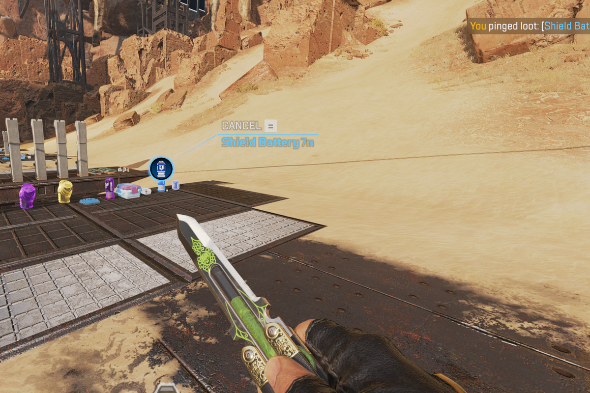 """Screenshot of Apex Legends, showing a dessert landscape and a hand holding a knife, with text in the upper right corner that says """"you pinged shield battery."""""""