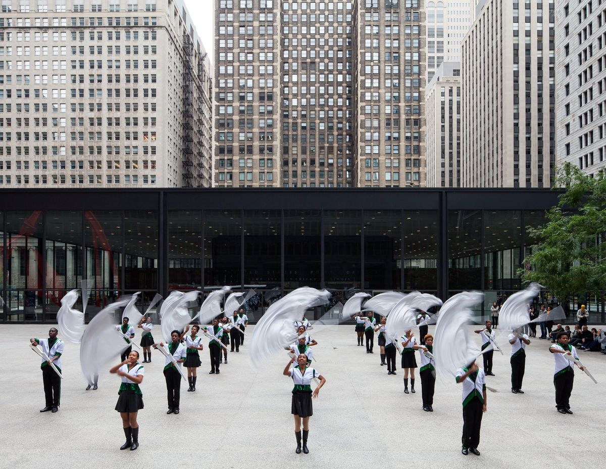 Members of a drill team, dressed in black and white, waving white flags, on a patio with tall grey city buildings behind them.