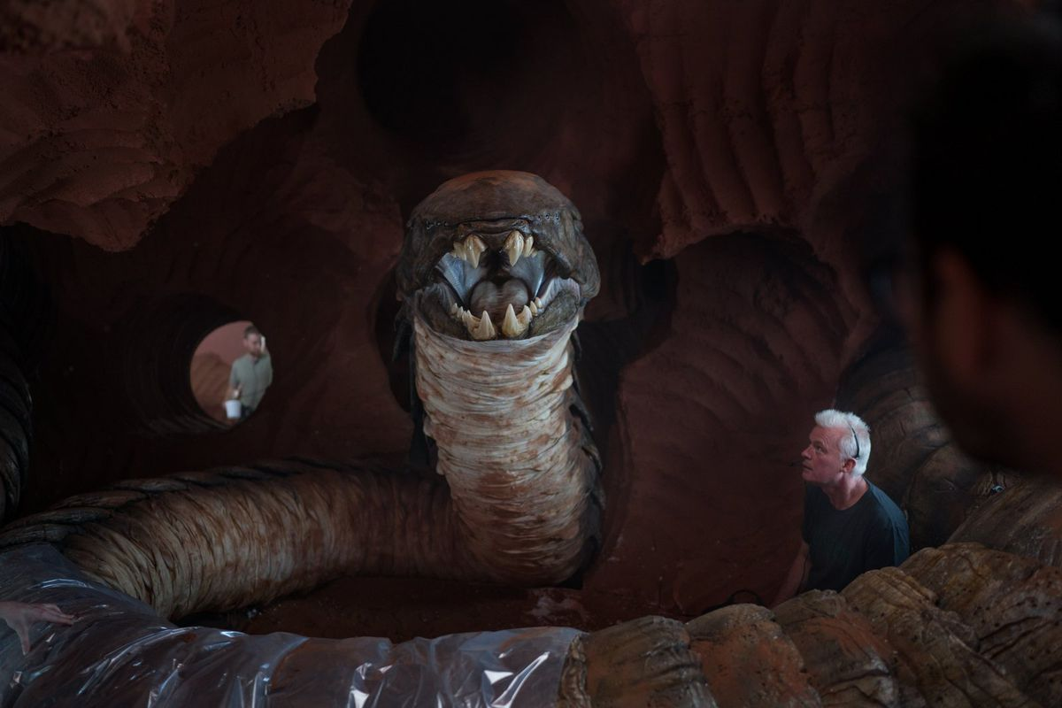 Rise of Skywalker creature SFX supervisor Neal Scanlan stands in an artificial cave, ringed by a gigantic serpent puppet, on the Rise of Skywalker set.