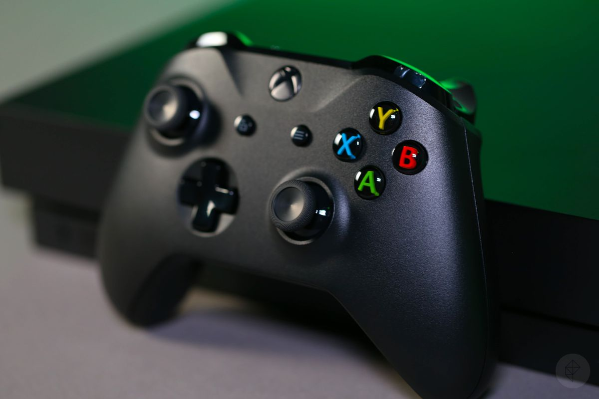 an Xbox One X controller standing in front of an Xbox One X