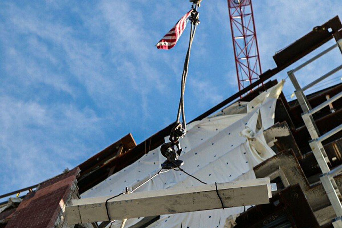 Looking up at a crane with a flag hoisting a beam in place on a building.