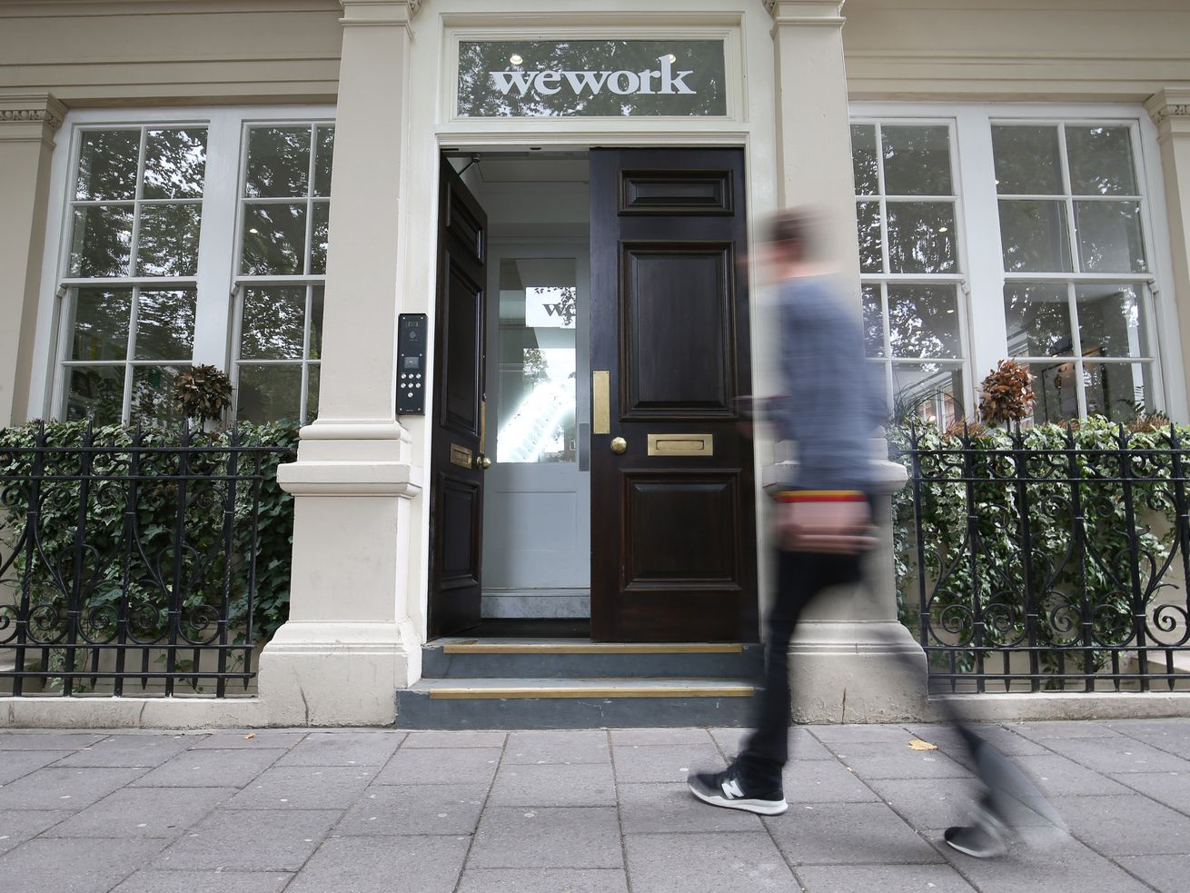 """A person walking across the sidewalk toward a building with """"WeWork"""" over the door."""