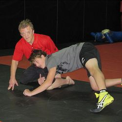 As he trains for the Olympics, Ben Kjar helps high school wrestler Zach Colangelo, 15, with his moves.