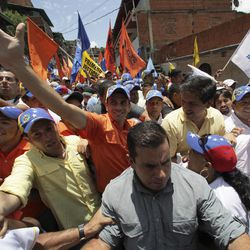Opposition's presidential candidate Henrique Capriles, center, greets supporters during a campaign rally in Caracas, Venezuela, Sunday, Sept. 16, 2012. Capriles is running against President Hugo Chavez in the country's Oct. 7 election.