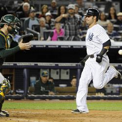 New York Yankees' Nick Swisher beats the throw to Oakland Athletics catcher Derek Norris to score on Curtis Granderson's sacrifice fly in the fourth inning of a baseball game Friday, Sept. 21, 2012, at Yankee Stadium in New York.