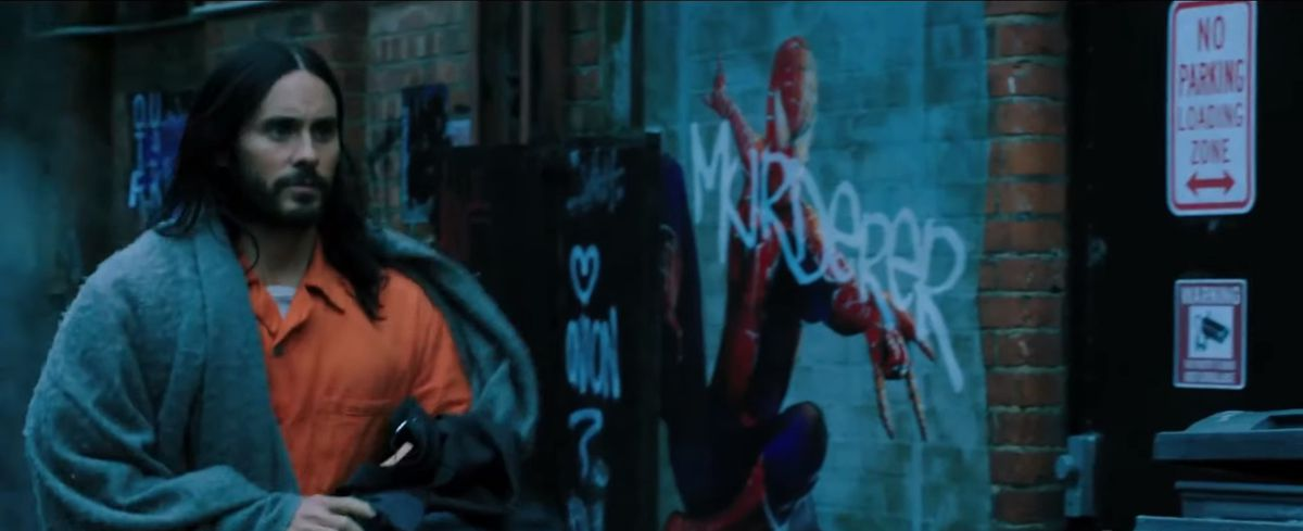Jared Leto's Morbius walks through an alley with a Spider-Man poster in the background