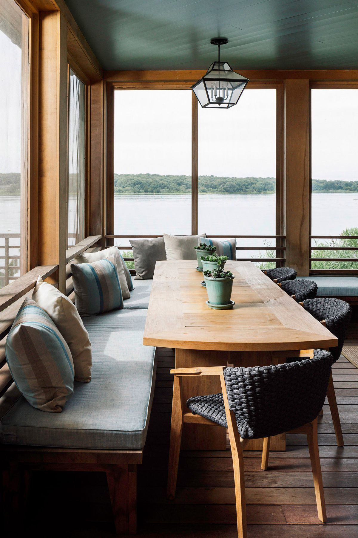 A screened in porch has a long table surrounded by a banquette and chairs.