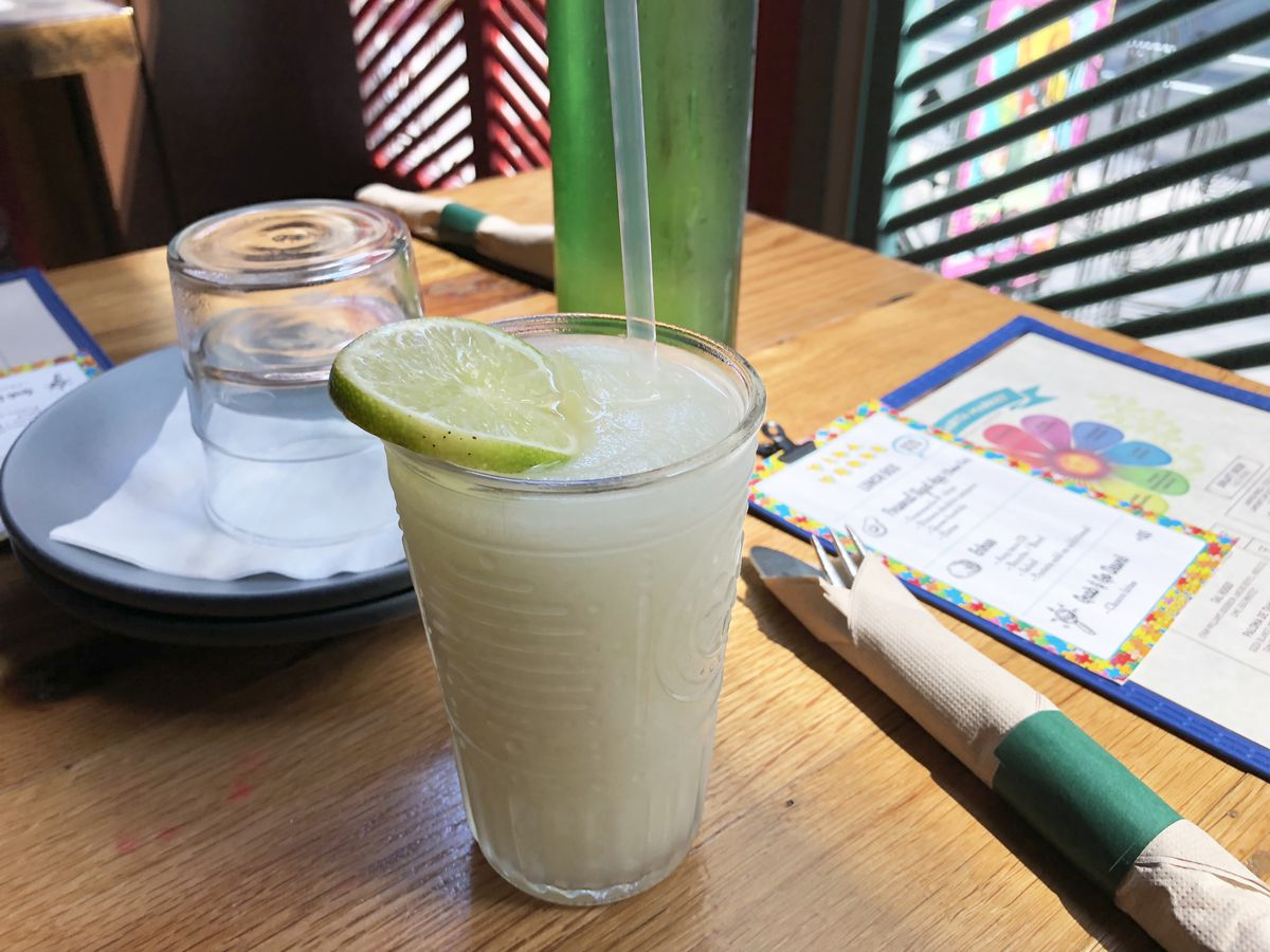 A frozen margarita at Vida Verde sits on a table next to a window