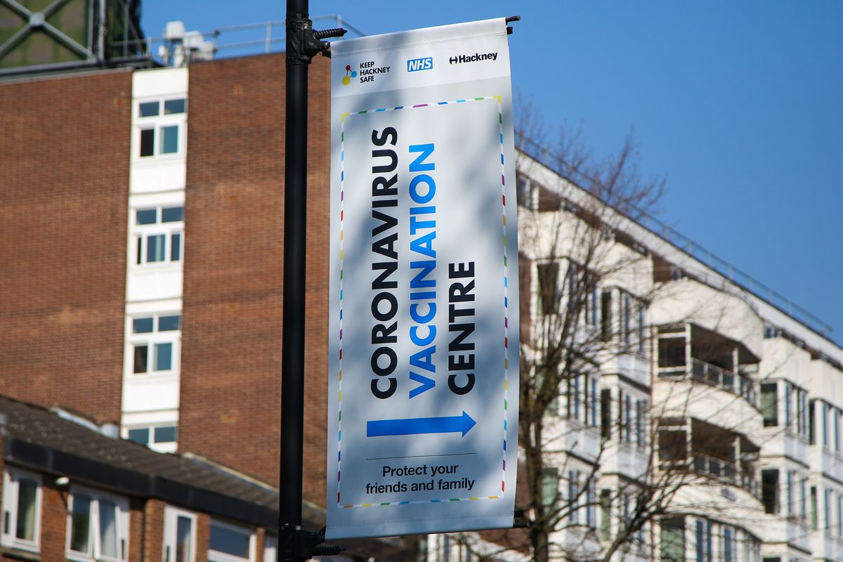 """A sign with an arrow hanging on the outside of a London building reads """"Coronavirus vaccination centre."""""""