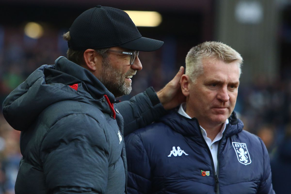 Jürgen Klopp and Aston Villa manager Dean Smith look on as their sides battle in the Premier League in 2019. Klopp has his hand on Dean Smith's neck as the two appear friendly. Both wear club-specific puff jackets as it is November and chilly.
