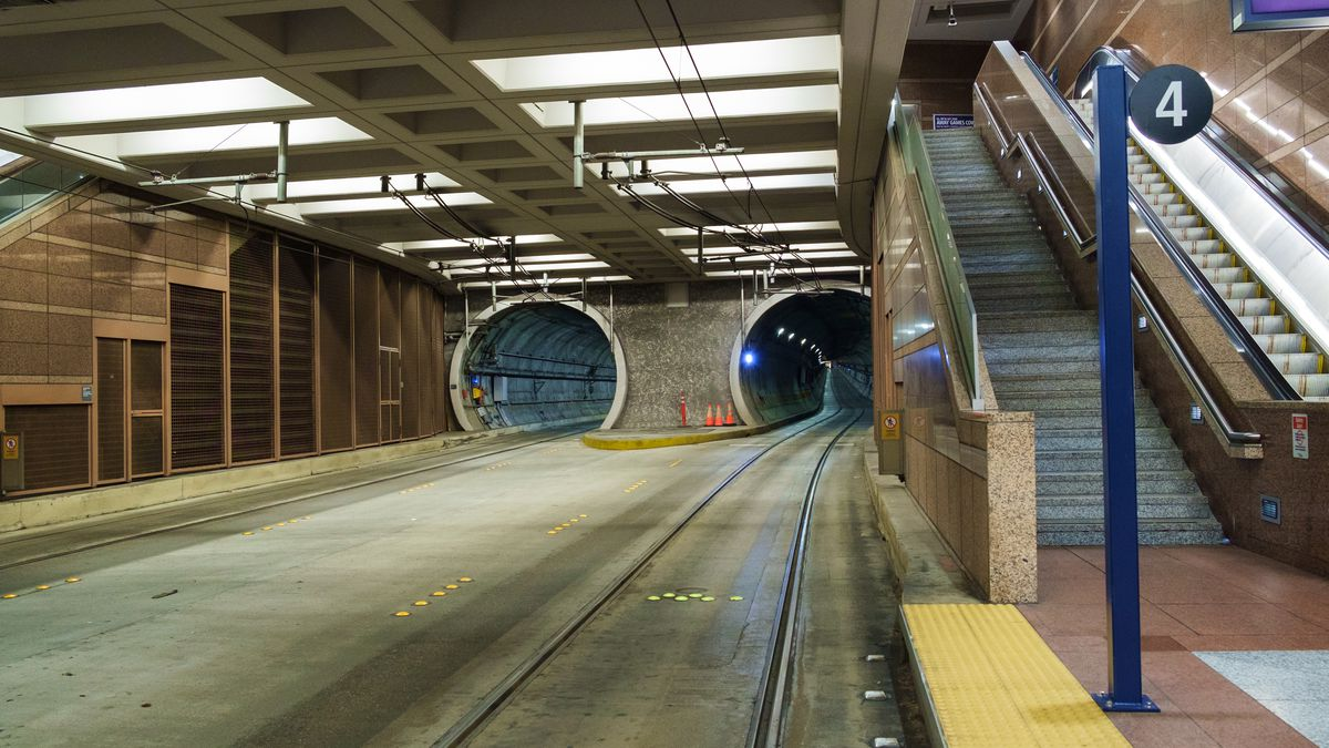 A large, underground tunnel. A platform to the right has stairs and an escalator leading up. To the left, train tracks lead into two round, narrower tunnels.