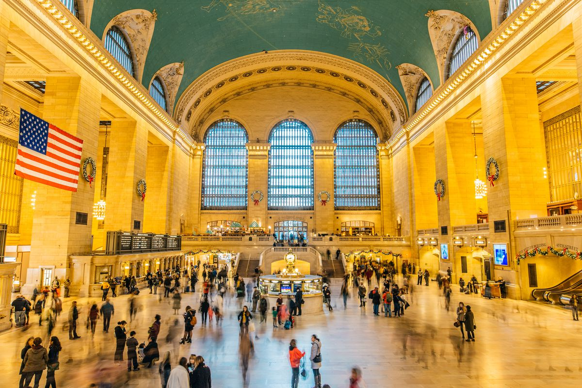 The main grand central terminal with a golden vaulted ceiling with green paint. Some people are seen walking inside the terminal.