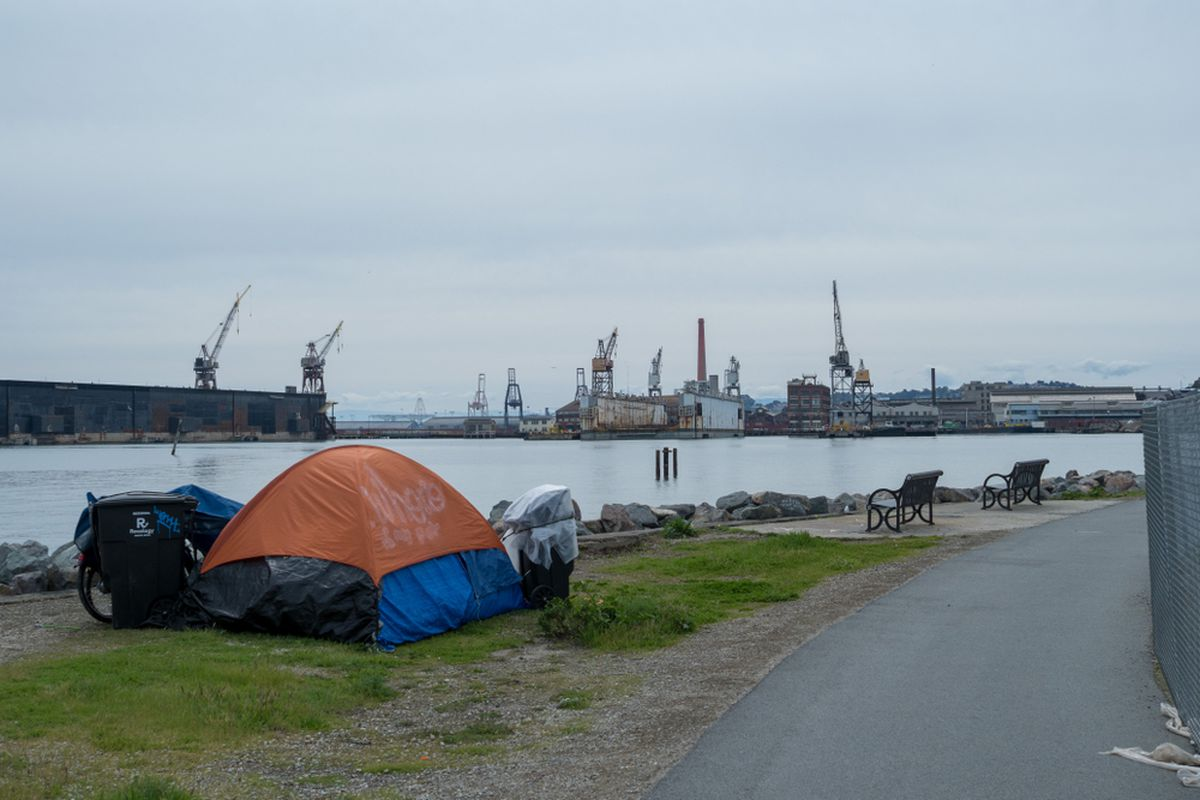 A an orange and blue tent camped along the Bay in San Francisco, with tall shipping cranes visible in the distance.