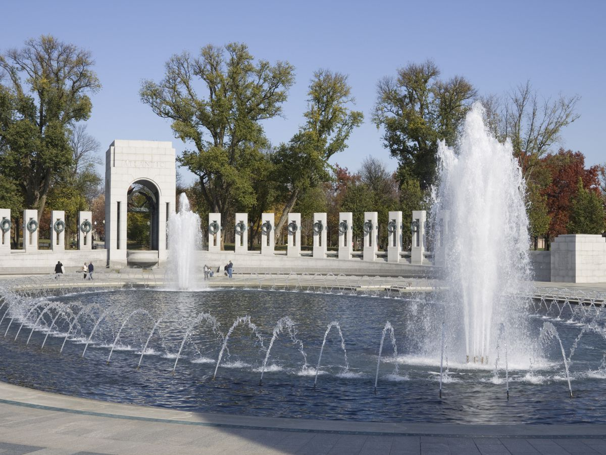 An oval fountain at the center of pillars with sculptural wreaths on their faces.