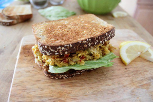 Seeded bread sandwich with curried chickpeas and lettuce on a wooden cutting board