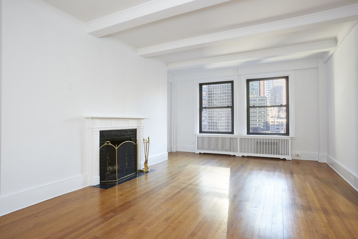 A living area with hardwood floors, beamed ceilings, two large windows, and a wood-burning fireplace.