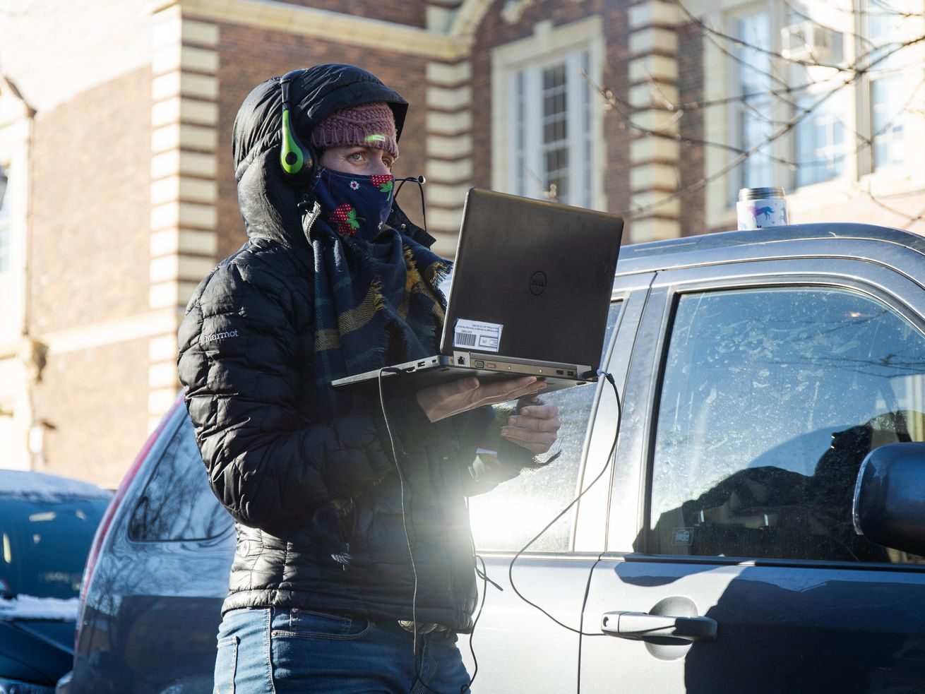 A teacher charges her laptop while teaching outside DeWitt Clinton Elementary School in the West Rogers Park neighborhood to protest Chicago Public Schools' reopening plan due to COVID-19 safety concerns, Thursday morning, Jan. 21, 2021.