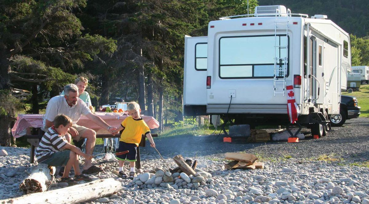 A family of two children and two adults sits on a picnic table and driftwood on a rocky beach roasting marshmallows in a fire. A motorized white motorhome sits in the background.