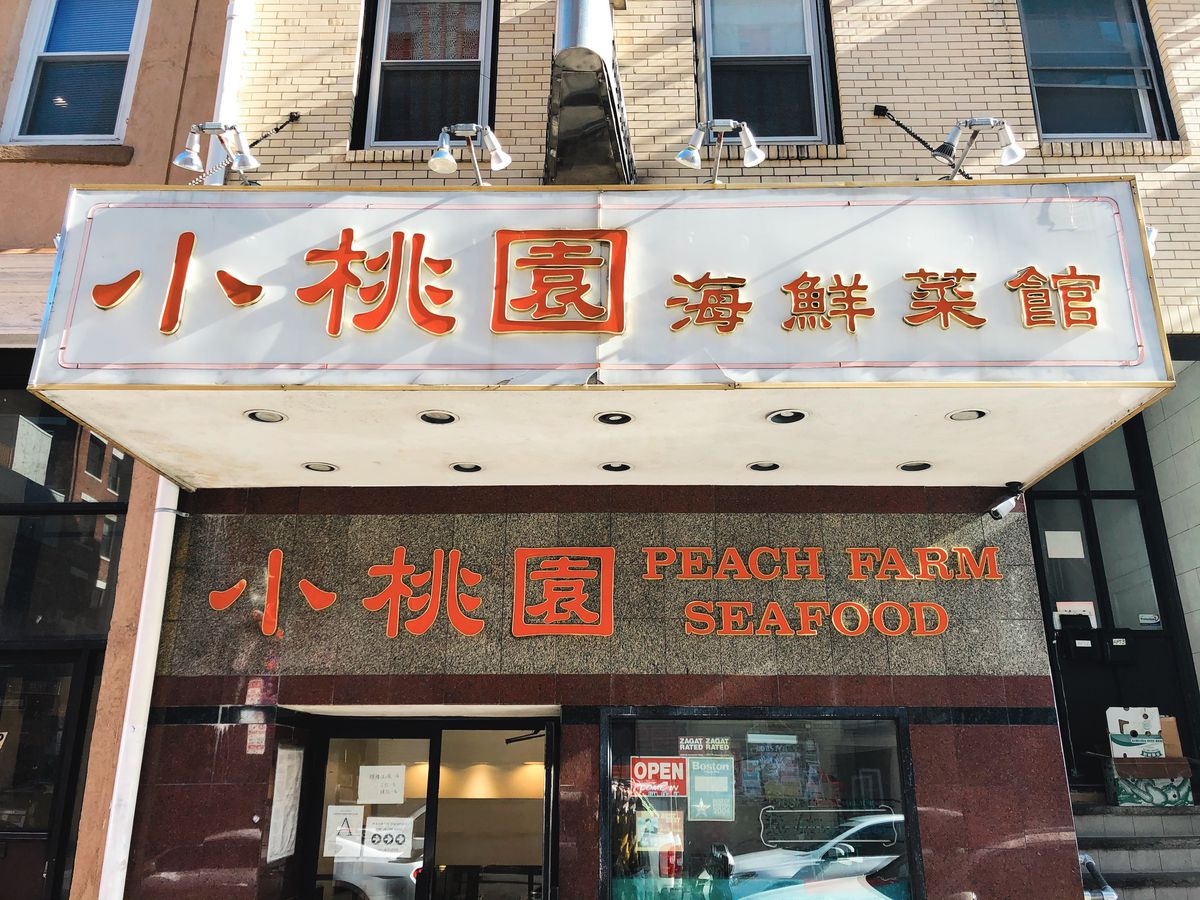 The facade of Peach Farm restaurant in Boston's Chinatown. The overhand is painted white with red Chinese characters.