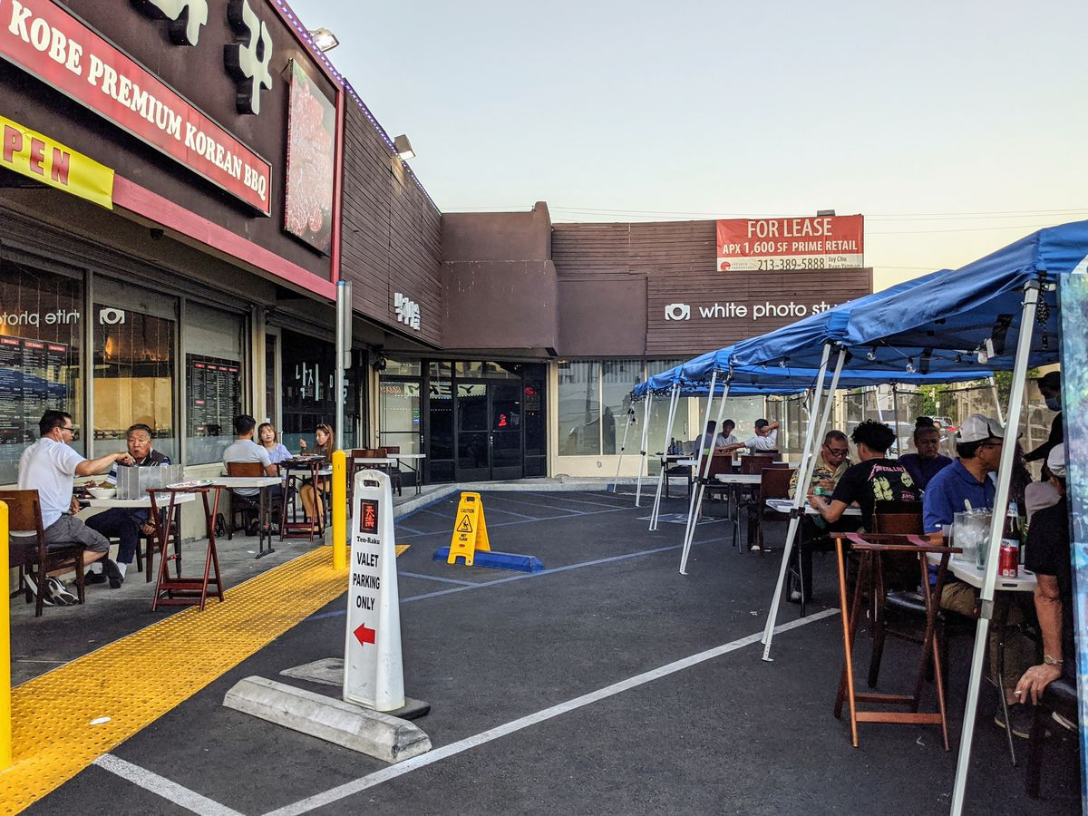 Outdoor dining setup at Tenraku in Koreatown with covered tables.