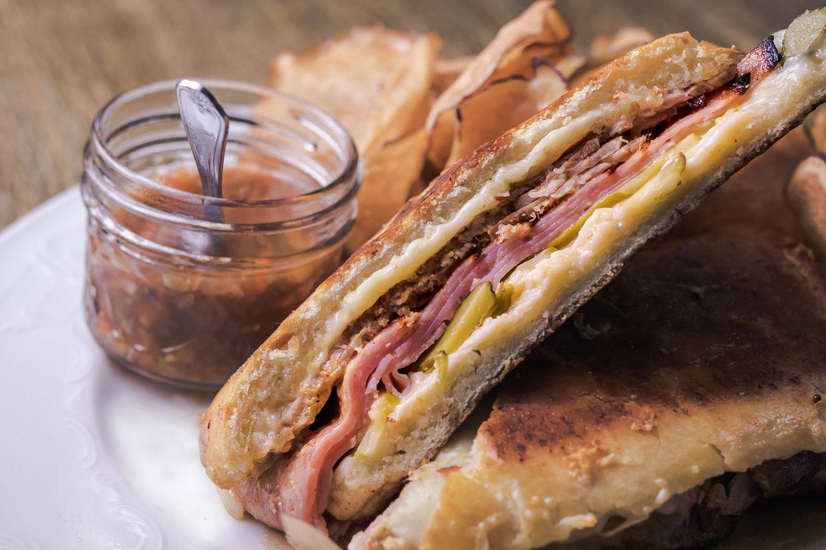 A Cuban sandwich with ham and mustard sits on a plate on a wooden table