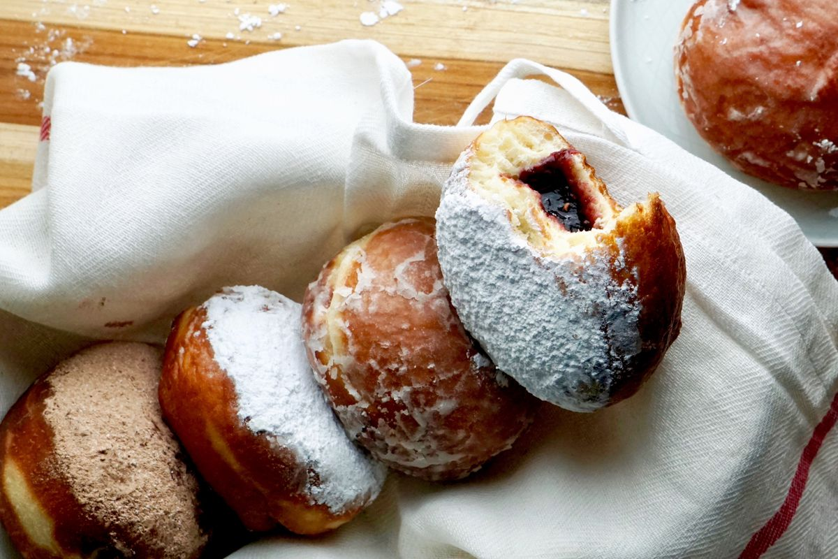Four paczkis siting on a white cloth napkin, two sprinkled with confectioners sugar and one with cinnamon sugar. The doughnut on the right has a bite taken out of it revealing jelly filling