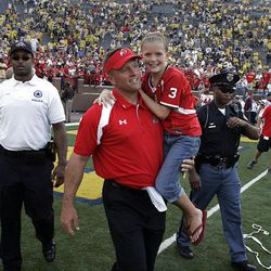 Coach Kyle Whittingham and daughter Kylie cross the field as Utah defeats the University of Michigan on Aug. 30, 2008.