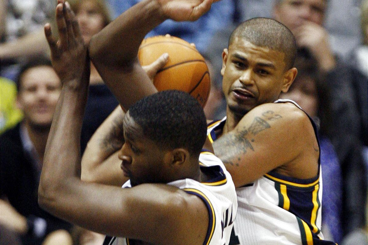 Utah Jazz point guard Earl Watson, at top right, pulls in a rebound as Utah Jazz small forward C.J. Miles gets out of the way.